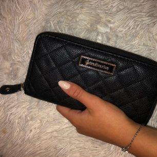 Supersnygg clutch/plånbok från Stradivarius i svart mönster.