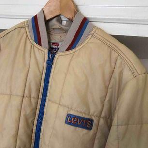 Väl använd vintage Levis täckjacka. Uppskattningsvis från tidigt 90-tal. En del fläckar samt fläckar av färg på ena armen. Fodret i sömmen bak på ryggen har hål. Trots detta en fräsig jacka. Kan hämtas i Uppsala eller skickas mot fraktkostnad