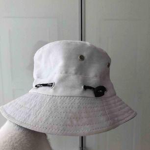 En vit buckethatt/ fiskehatt. Vet ej märket då den är köpt utomlands.
