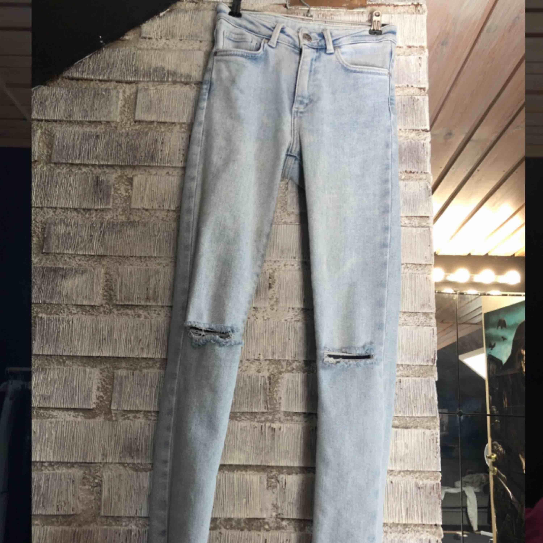 Skitsnygga ljusblå jeans från Bikbok. Hål i knäna, slitna detaljer längst ner vid fötterna, sitter perfekt. Säljer pga att de aldrig kommer till användning. Nypris 599kr.. Jeans & Byxor.
