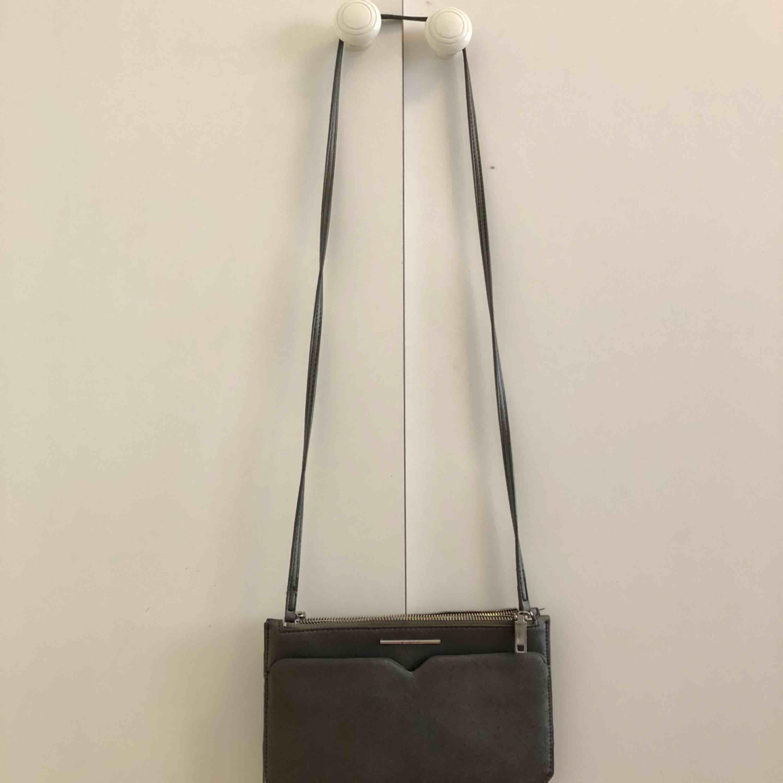 Söt axelremsväska från Mango, aldrig använd. Smidig och rymmer en del då den har ett flertal olika fack. Grå med silver detaljer. . Väskor.