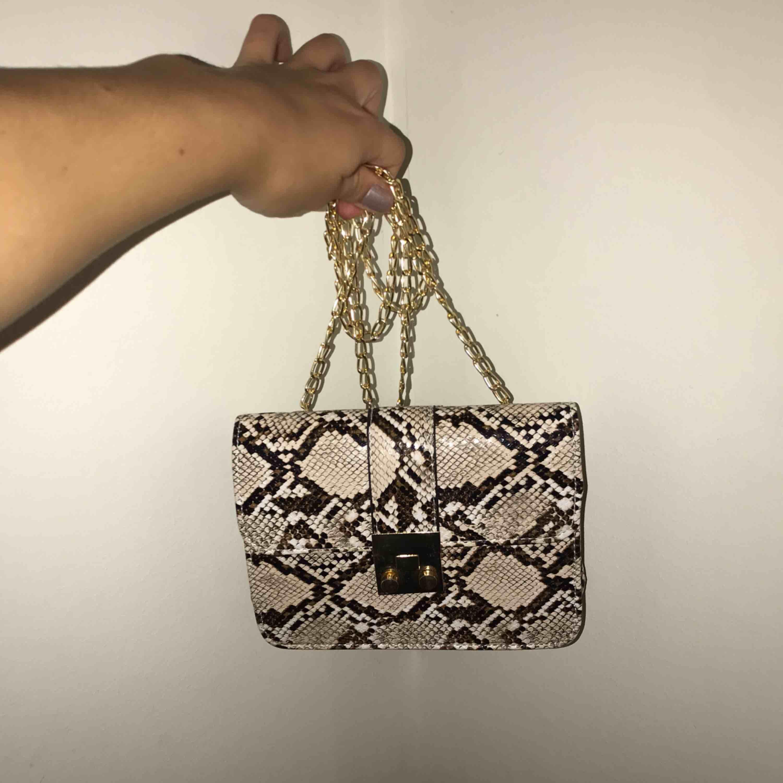 Helt ny (i förpackning). Supersnygg väska i fake mönstrat ormskinn! Frakt tillkommer! . Väskor.