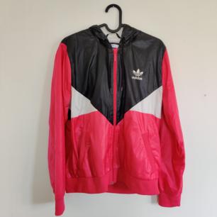 Vindjacka från Adidas med luva. I väldigt bra skick. På bilden ser färgen lite rosa/röd ut men i verkligheten är den knallrosa. Kan hämtas i centrala Uppsala eller fraktas inom Sverige. Vid frakt står köparen för fraktkostnaden. Betalning kan ske via Swish!