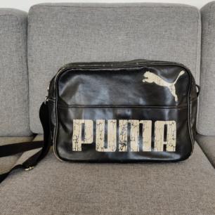 Svart axelremsväska i fejkskinn från Puma med måtten 40x30x15, alltså en tillräckligt stor väska för att få ner en laptop och anteckningsblock osv. I använt skick med skav på vissa ställen (se bilder), personligen tycker jag dock att det bara tillför till looken av väskan. Det finns ett ytterfack med kardborre band som förslutning, samt ett stort innerfack med dragkedja på ena sidan och två mindre öppna fack på motsatt sida på insidan av väskan.  Kan hämtas i centrala Uppsala eller fraktas inom Sverige. Vid frakt står köparen för fraktkostnaden. Betalning kan ske via Swish!