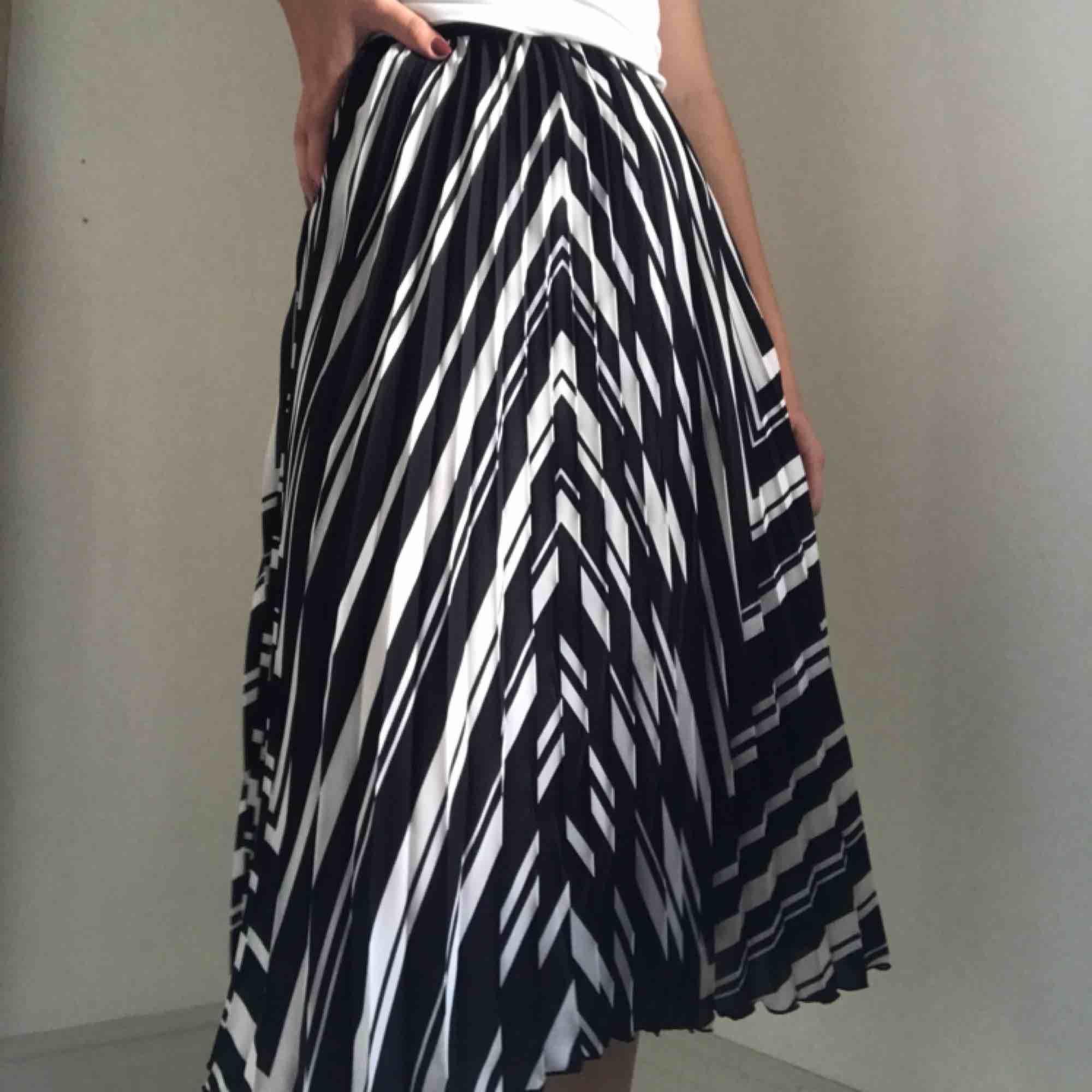 Vit och svart plisserad kjol från H&M. Använd ett par enstaka gånger, fint skick. Köparen står för frakten💛. Kjolar.