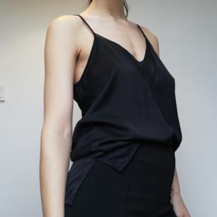 Svart v-ringat linne med tunna spagettiband och see-through parti med slitsar från Zara Collection. Stl M men snygg på mindre storlekar också. Frakt 42 kr.