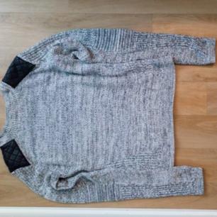 Begagnad stickad tröja med skinndetaljer. Endast använd ett fåtal ggr. Frakt tillkommer