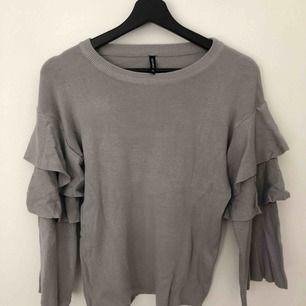 Grå finstickad tröja med volanger på ärmarna. Endast använd 1 gång. Den är i väldigt fins skick.