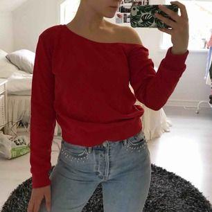 Klarröd sweatshirt från NA-KD som är skuren så att den blir off shoulder på ena axeln, frakt ingår i priset :)