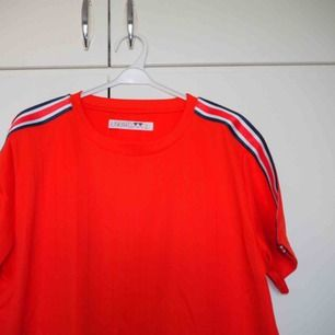 Tshirt i glansigt tyg (som en fotbollströja). Från Junkyard.  En damstorlek L. Mer lik en Medium. 💥 Använd 1 gång.