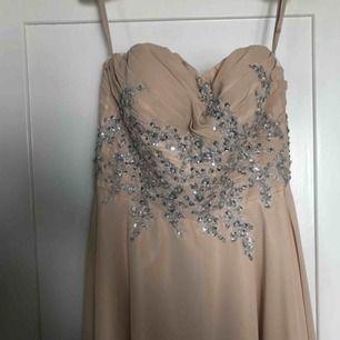 Beige, champagnefärgad balklänning med glittriga stenar på.Ursprungspris 2500, använd en gång.  Några små skavanker som jag kan skicka bild på vid intresse, även särskilda mått och fler bilder på klänningen finns! Kan mötas upp eller skicka för 100kr.😊