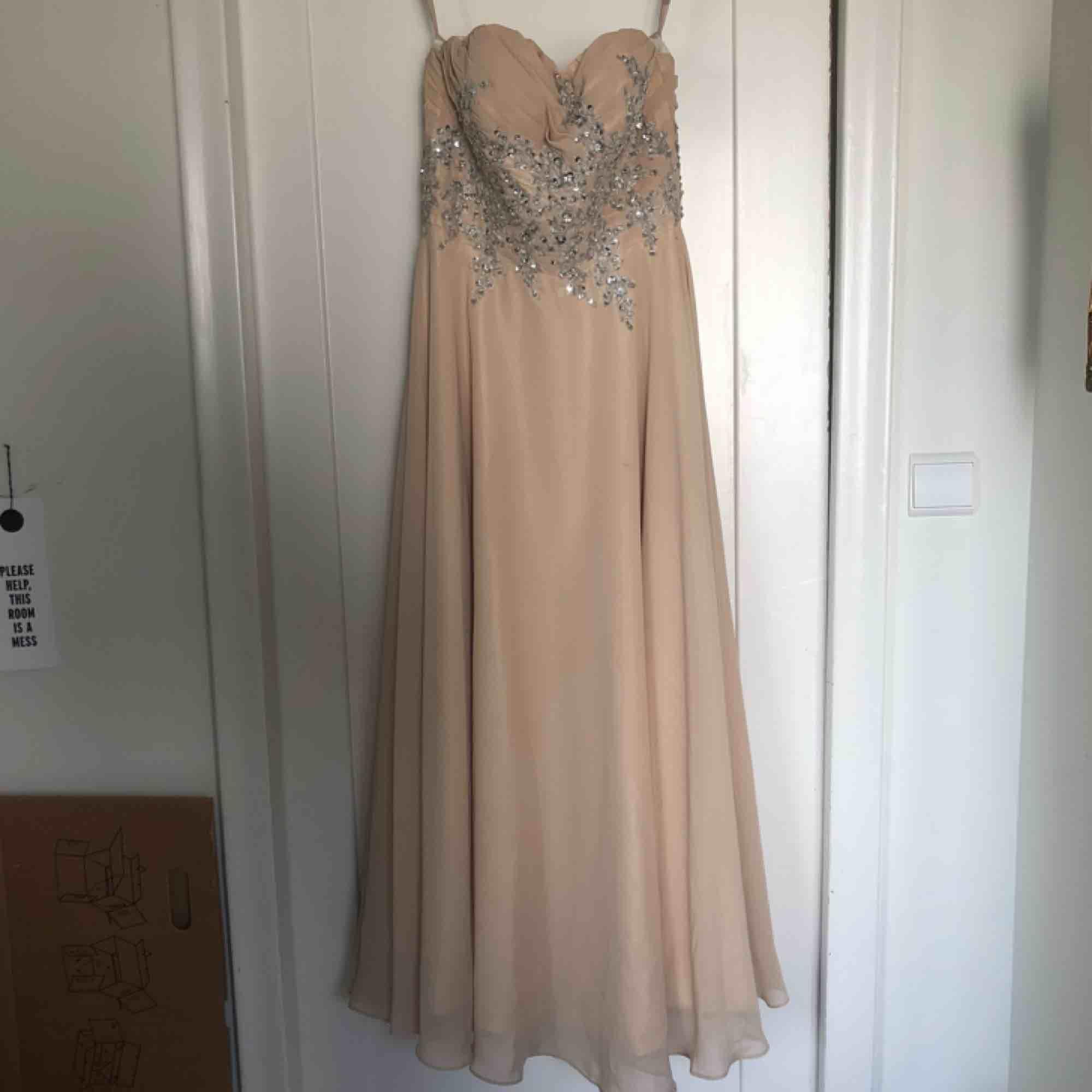 Beige, champagnefärgad balklänning med glittriga stenar på.Ursprungspris 2500, använd en gång.  Några små skavanker som jag kan skicka bild på vid intresse, även särskilda mått och fler bilder på klänningen finns! Kan mötas upp eller skicka för 100kr.😊. Klänningar.