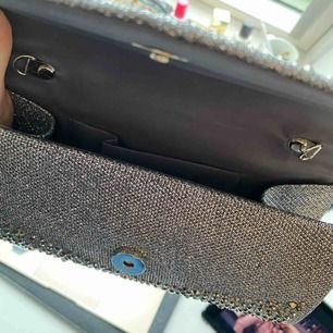 Glittrig silver clutch från en butik i USA. Aldrig använd och i bra skick. Skriv för mer info/bilder, frakt är inkluderat i priset.