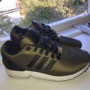 Guld och svarta skor från adidas, adidas torsion. Använda fåtal gånger, ser ut som nya.  Kan mötas upp eller skicka för 75kr.😊