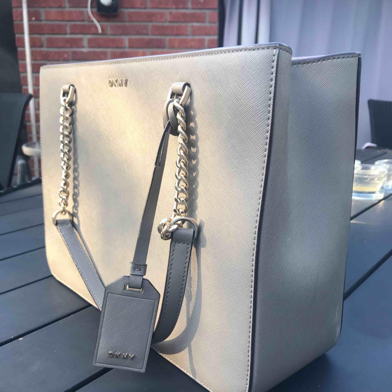 En nästan helt oanvänd DKNY väska i färgen grå. Den var med om en liten olycka som brände insidan av väskan lite men ingenting är trasigt. Kontakta gärna mig för bilder på insidan. På utsidan så ser den helt ny ut. Pris går att diskutera vid snabbt köp! . Väskor.