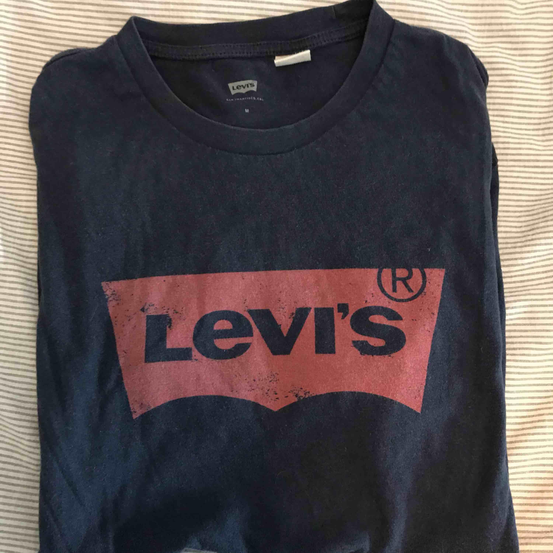 Levi's tröja i marinblå med rött tryck, bra skick. T-shirts.