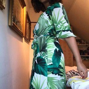 Kortklänning med palmmotiv, luftigt och skönt material!  Ger fin figur, kort krage och mycket urringning (har satt säkerhetsklämma)