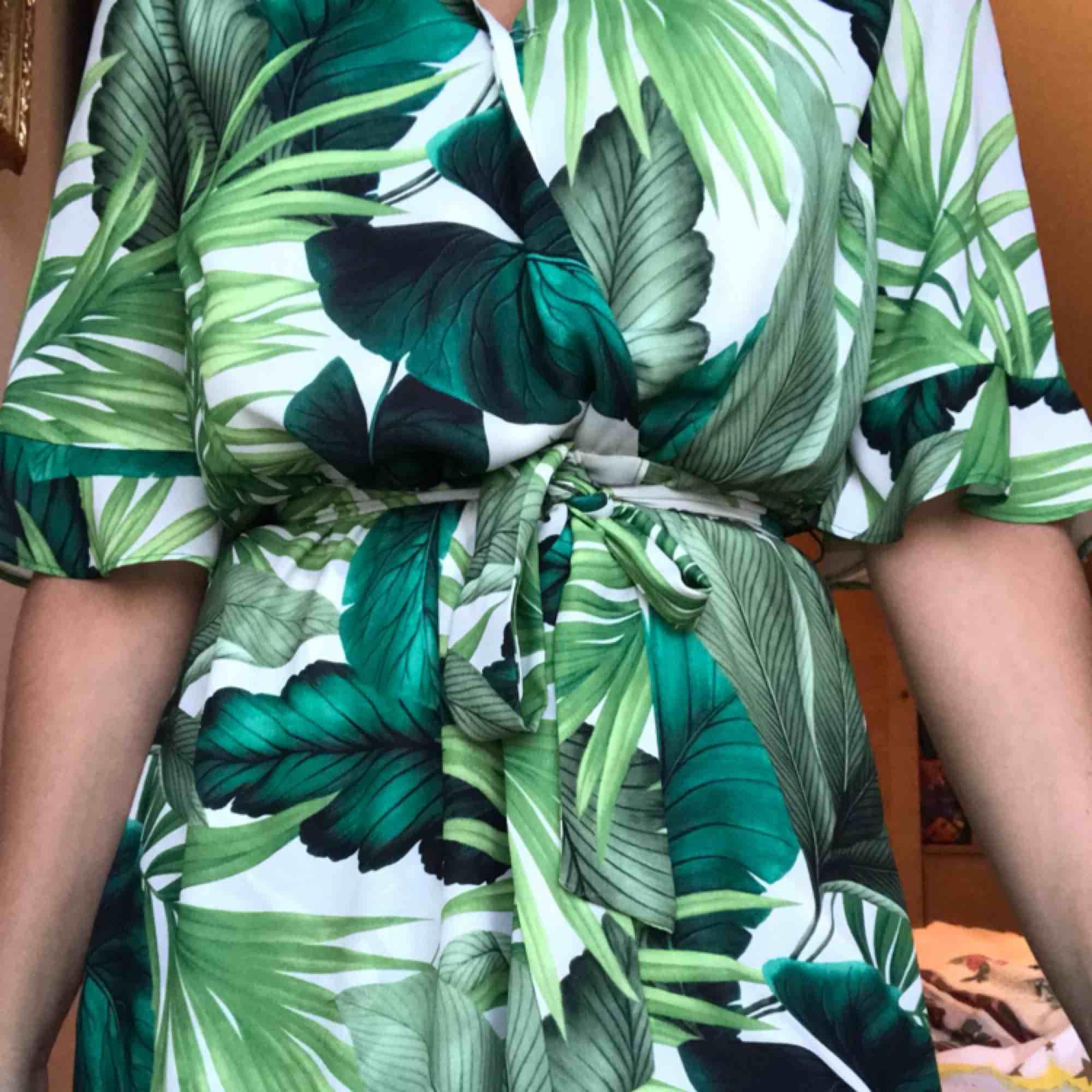 Kortklänning med palmmotiv, luftigt och skönt material!  Ger fin figur, kort krage och mycket urringning (har satt säkerhetsklämma) . Klänningar.