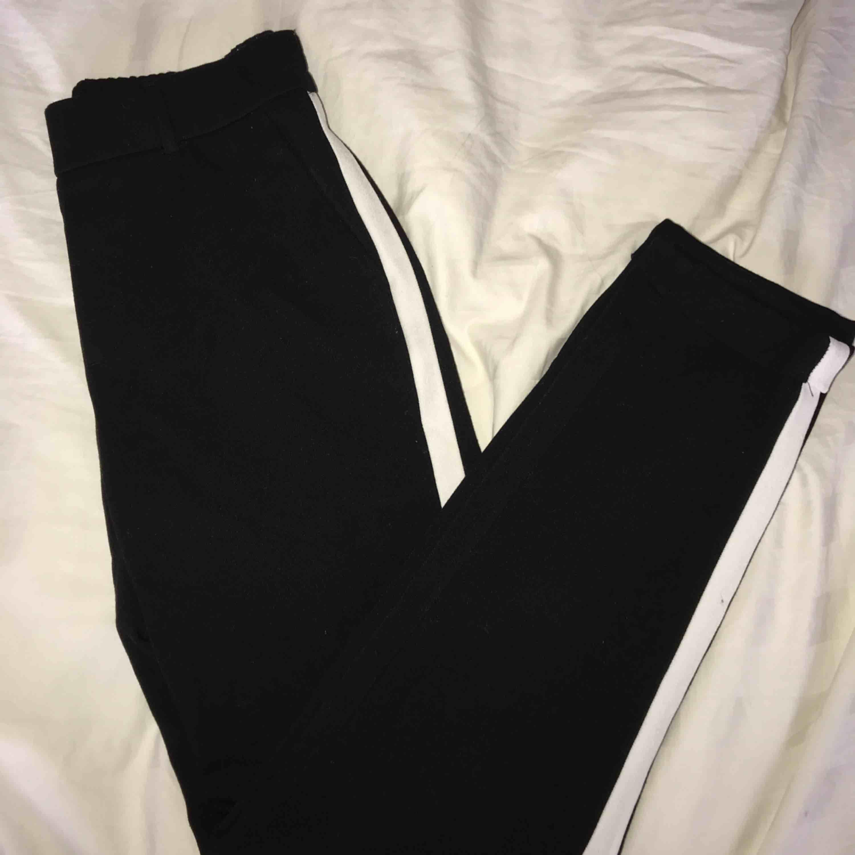 Ett par svarta kostymbyxor med vita ränder på sidorna från Vero Moda. Lite kortare i modellen. Använda 2-3ggr så därför väldigt fint skick!! Inköpta för cirka 199kr säljer för 99kr. Köpare står för frakt🥰🥰🥰. Jeans & Byxor.