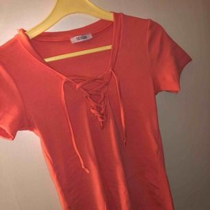 En rosa klänning med snörning, likadan som klänningen ovanför men kortärmad och även en t-shirt, ingen storlekslapp på men skulle gissa på en S som klänningen!