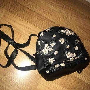 Säljer denna lilla ryggsäck, den har brodyr på med rosa och vita blommor på sig. Det får plats mycket i den och den är i fint skick! Man kan ändra banden på ryggen så den kan bli till en vanlig väska.
