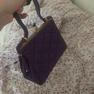 En lila handväska med gulddetaljer, köpt från second hand men har aldrig använt den tyvärr.