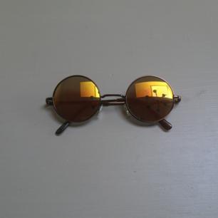 Runda solglasögon med gul/orange/grönt glas.