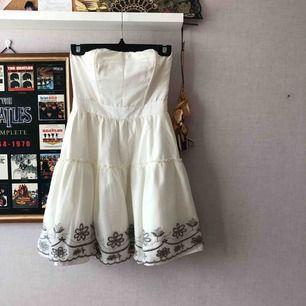 Vit axellös klänning med grå detaljer