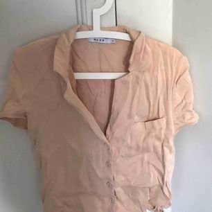 En fin silkes skjorta/blues från NA-KD i stolek 38 men passar även 36/34 beroende på hur man vill att den ska sitta. Nästan helt oanvänd och säljes pga att jag har 2.