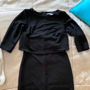 Svart klänning med liten volang vid brösten. Svart med lite mönster i tyget. Frakt inräknat