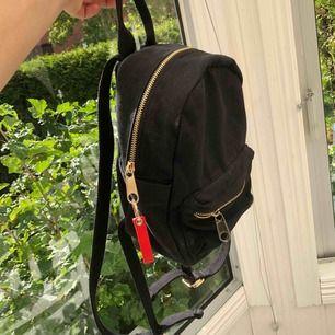 Svart liten ryggsäck i tyg från urban outfitters. Inte använd så många gånger, bra skick. (Det är endast lite damm som ser smutsigt ut på bilden. Den ska tvättas innan jag skickar iväg den☺️)