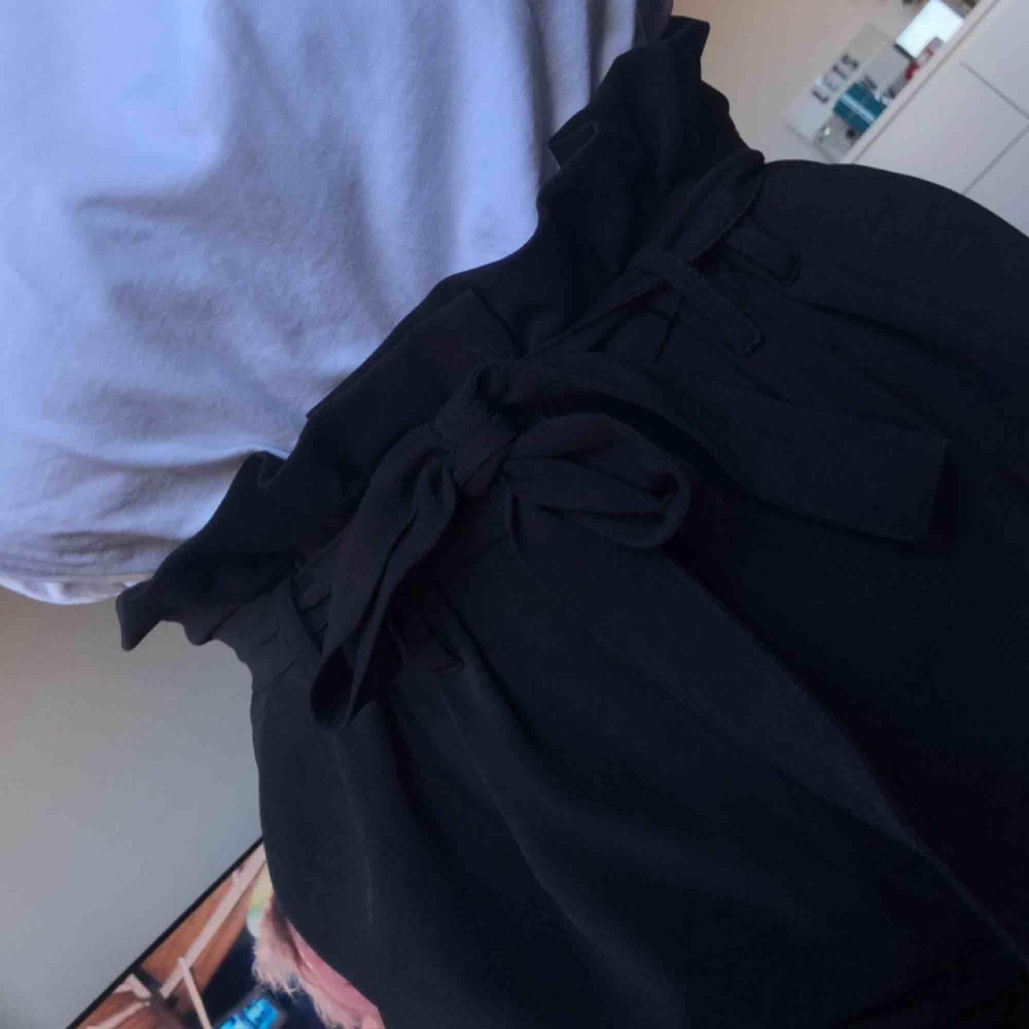 Svarta högmidjade kostymbyxor med knytning i midjan. Raka i modellen. Frakt ingår. Jeans & Byxor.