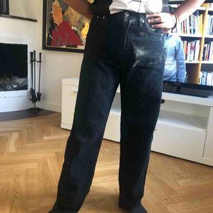 Svarta 90s baggy Levis jeans. Raka jeans i en baggy modell. Personen på bilden är 152 och jeansen nuddar golvet. Jag är själv 167 och då är dom lite över ankeln. Jeansen passar på ngn mellan storlek 25-27. Använda fåtal ggr! Köpta för 900kr