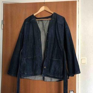 Jättefin kimono jeansjacka med knyt från other stories knappt använt så super fint skick. Står stl 34 men passar både s-m beroende på hur man vill att den ska sitta.