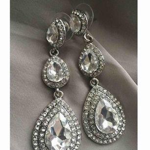 Säljer nu dessa eleganta örhängena helt nya i sin förpackning.  Färg: Silver  Längd: 6 cm Originalpris : säljes för ca 299-399:- beroende på vilken bröllops och festklänningsbutik / online smyckesbutik man väljer ifrån.