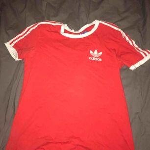 Röd adidas t-shirt , köpt på humana och använd fåtal gånger. Lite smutsigt/dammigt adidas märke men inget som man tänker på. Annars bra skick.