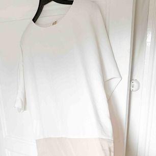 En klänning som är vit upptill och beige nedtill. Står varken storlek eller märke men skulle uppskatta att storlek är S-M. Dock har jag använt den som oversized! Tyget är glatt.