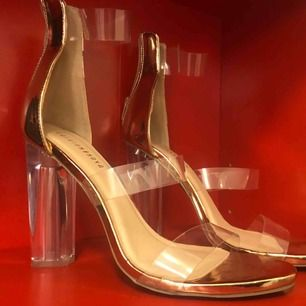 Guldfärgade skor (lite mer åt det rosé hållet) med genomskinlig stjock klack från fashion Nova. Original pris 400. Har endast använt en gång. Dom är lite tajta så skulle passa 39.