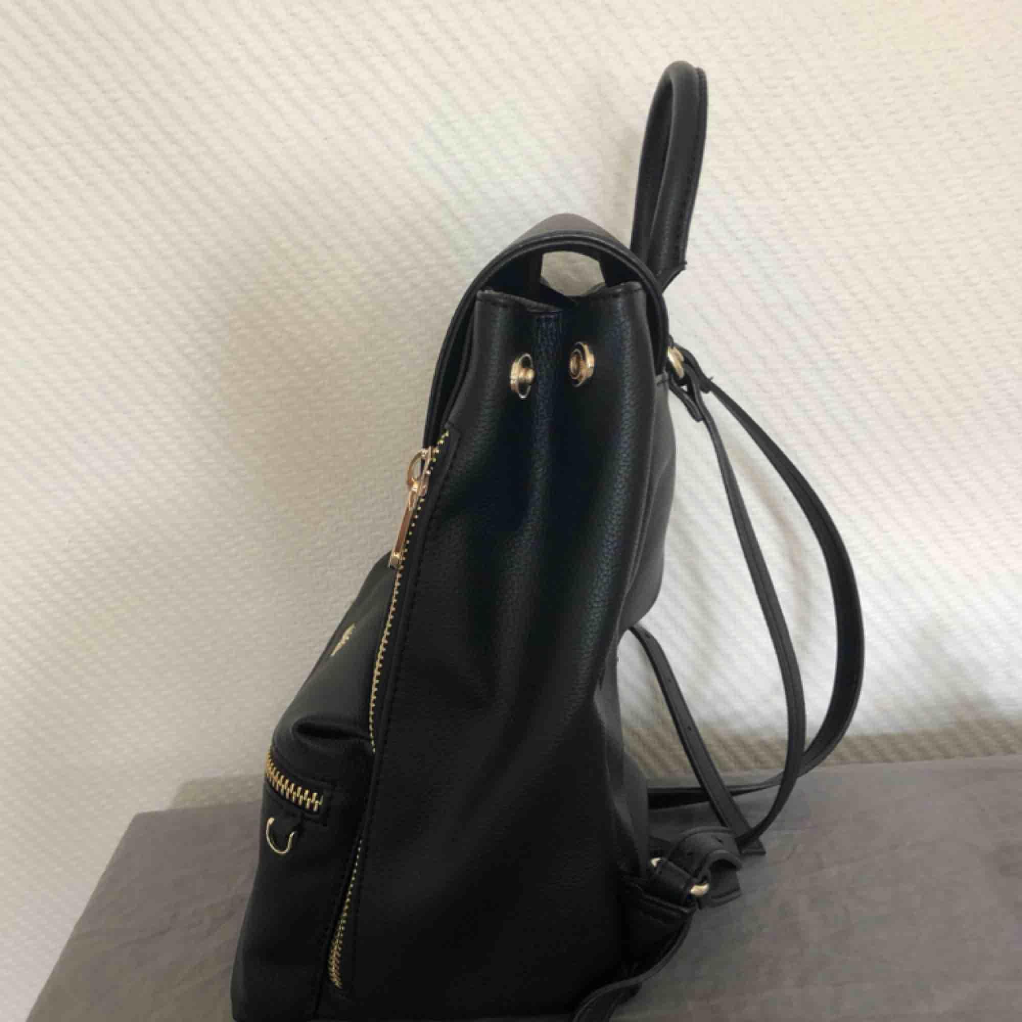 En helt oanvänd ryggsäck från Guess, nypris 999kr. Fått som present men har enbart stått i min garderob.  Ryggsäcken har många bra fack och är gjord av skinnimitation!. Väskor.