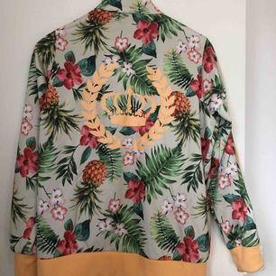 Tropiskt mönstrad polyester tröja i härliga färger. Väl använd men är i fint skick