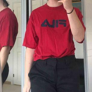 Avklippt FILA T-shirt, röd med marinblå text över bröstet. Avklippningen har inte påverkat längden, utan sitter stort.