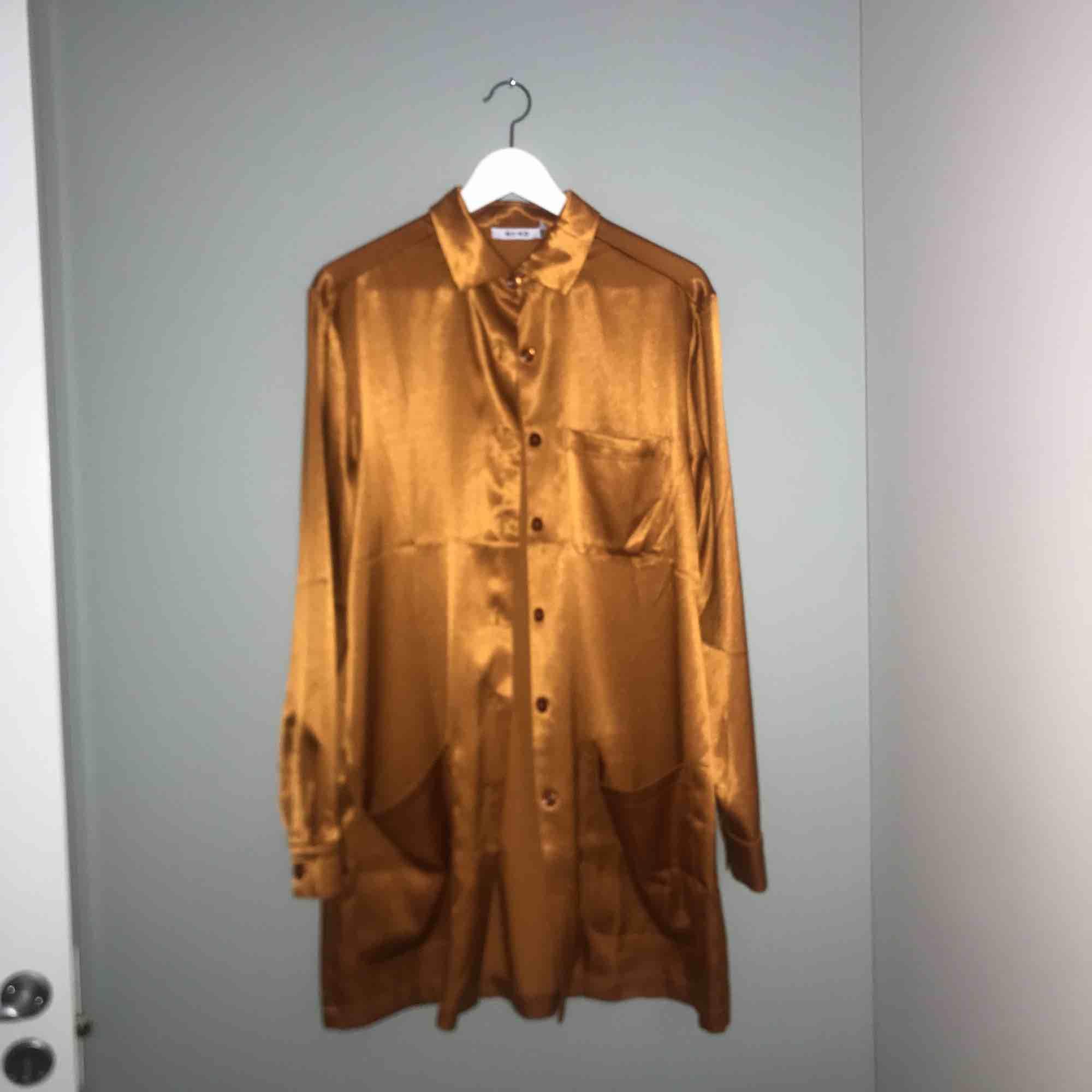 Lång superfin silkblus i orange/guldig färg (frakt kan tillkomma). Skjortor.