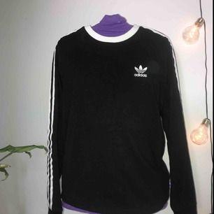 En svart/vit långärmad Adidas tröja. Nästan helt oanvänd, säljs pågrund av ingen användning. Inget fel på tröjan, jätte fin!köptes på Zalando för 489kr Nypris: ca 400kr