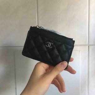 Chanel korthållare/mini plånbok (inte äkta) säljes! Får plats med 3 kort på baksidan, 1 på framsidan och så finns det en ficka med dragkedja där man kan lägga kontanter/kvitton/fler kort! Spårbar frakt tillkommer på 49kr!