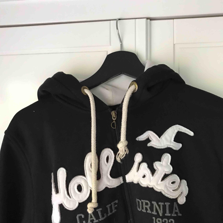 Svart fake Hollister hoodie köpt utomlands. Stor och mysig. Inte använd mycket alls och säljer eftersom det inte är min stil :) Står xxl på lappen men skulle säga att det är en M. Köparen står för frakt.. Huvtröjor & Träningströjor.