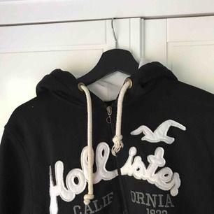 Svart fake Hollister hoodie köpt utomlands. Stor och mysig. Inte använd mycket alls och säljer eftersom det inte är min stil :) Står xxl på lappen men skulle säga att det är en M. Köparen står för frakt.