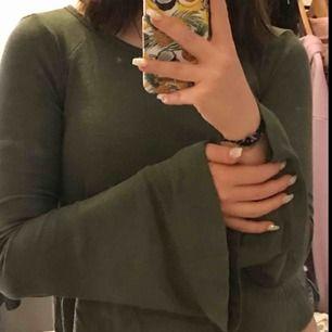 Grön tröja med utsvängda armar, och en öppen rygg, man kan ha en vanlig bh utan att det syns!