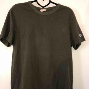 En mörkgrön Champion T-shirt, aldrig använd men ett pyttelitet hål (se bild 3) på bröstet av tröjan, storlek S (herr storlek)