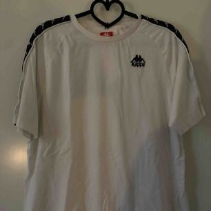 Vit Kappa T-shirt med en blå revär på ärmen, storlek L, använd men bra skick!