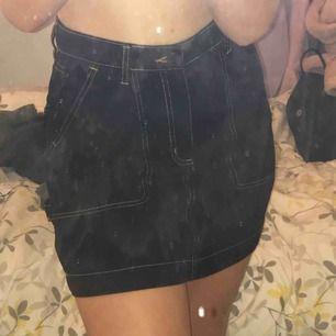 En svart kjol med beiga/oranga sömmar, använd 1 gång🤩
